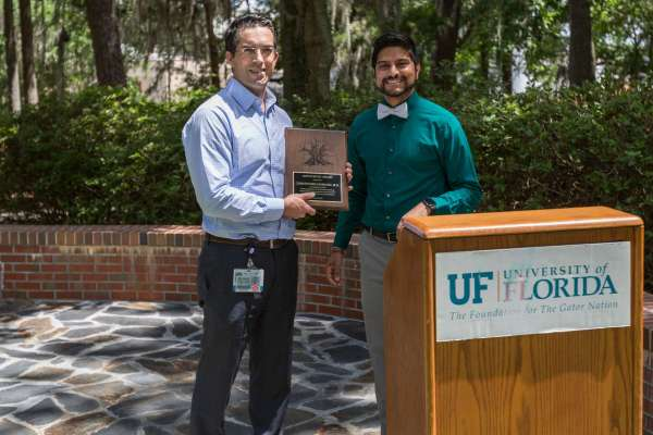 Dr. CHristopher Giordano accepts the Hippocratic Award from student Gabriel Daniels in Wilmot Gardens