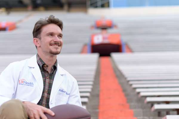 Mike McNeely sits on the bleachers in the stadium wearing a UF Health white coat and holding a football
