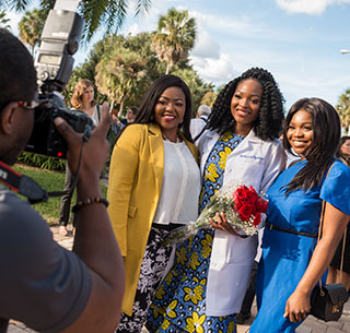 Student poses for photo with loved ones after white coat ceremony
