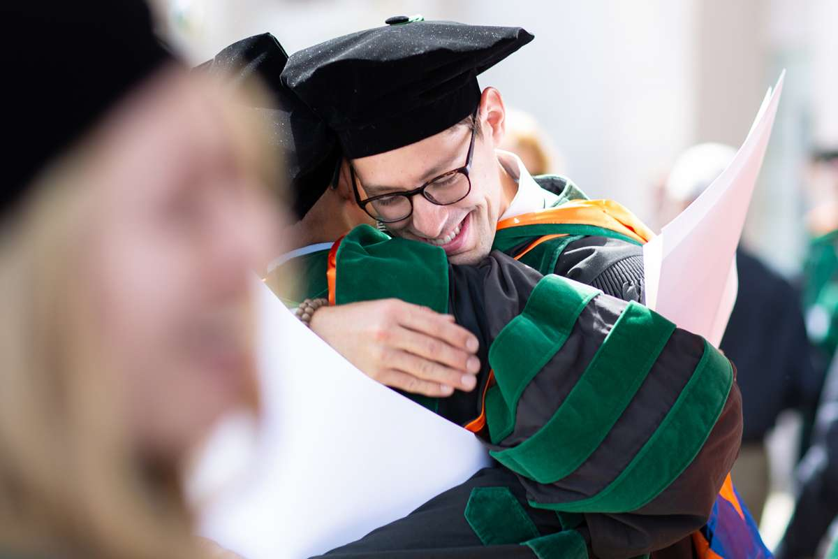 Graduates hug after commencement