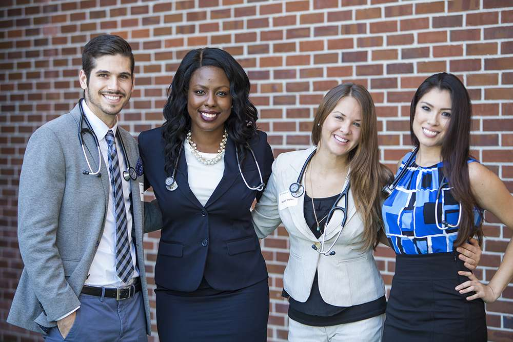 Four students smile at camera with stethoscopes