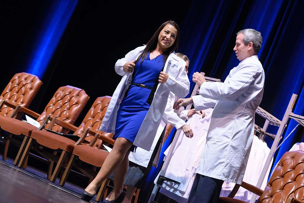 Student puts on white coat on stage