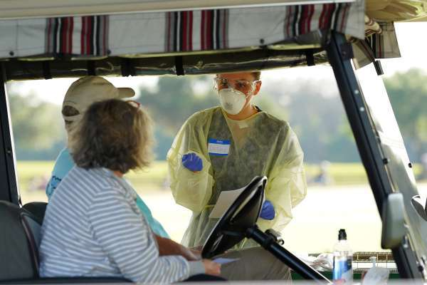 A volunteer wearing personal protection equipment asks screening questions to two people sitting in a golf cart