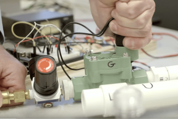 Hands assemble a ventilator made from hardware store parts