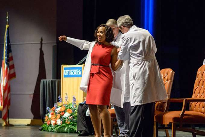 Two faculty members help a student put on her new white coat.