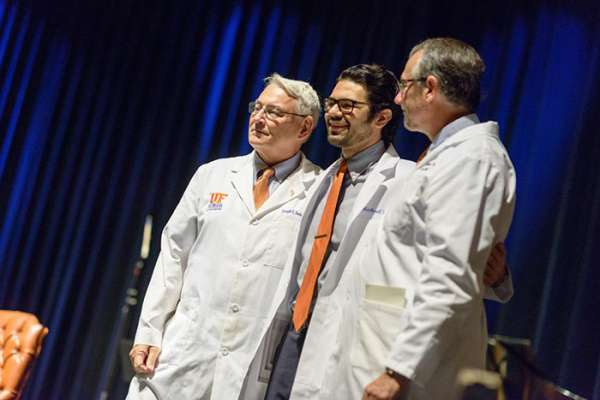 Two faculty members pose with a student while wearing his new white coat.