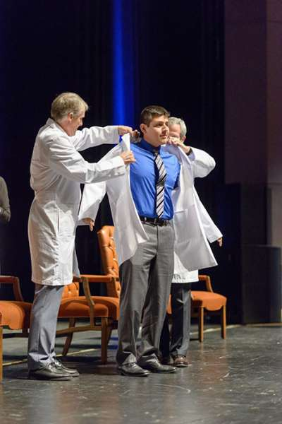 Two faculty members help a student put on his new white coat.