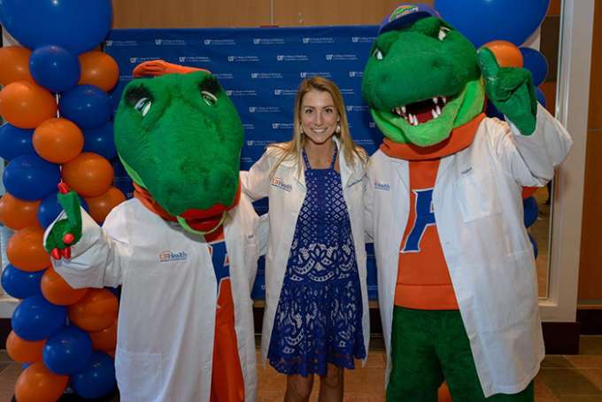 A student poses with U-F mascots Alberta and Albert Gator while wearing white coats