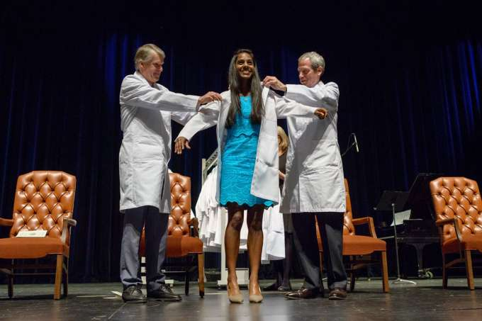 Class of 2020 White Coat ceremony - student receives white coat on stage