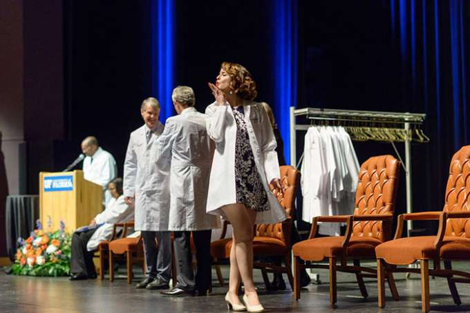 A student blows a kiss to her loved ones as she crosses the stage after receiving her new white coat.
