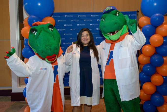 Class of 2020 white coat ceremony - student after ceremony wearing white coat with Albert and ALberta mascots