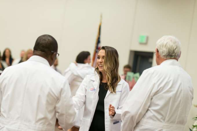 A student shakes a faculty member's hand after receiving her new white coat.