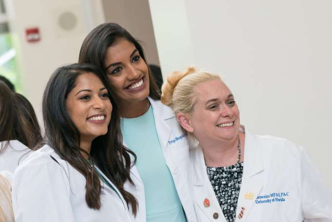 Two students pose with a faculty member while wearing their new white coats.