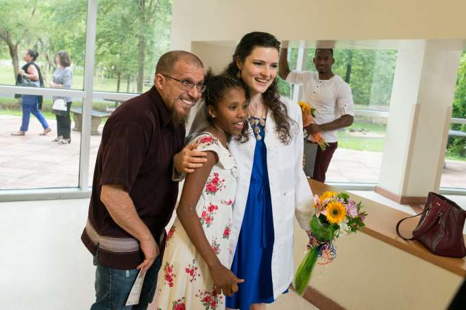A student poses with two of her loved ones while wearing her new white coat.