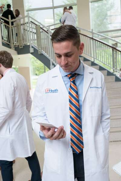 A student looks down at a notecard with words of advice from a UF graduate while wearing his new white coat.