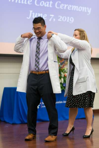 A faculty member helps a student put on his new white coat.
