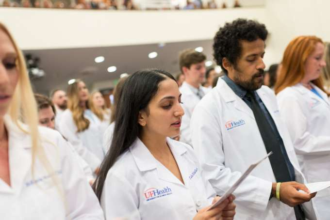 A row of students recite an oath from the white coat ceremony program.