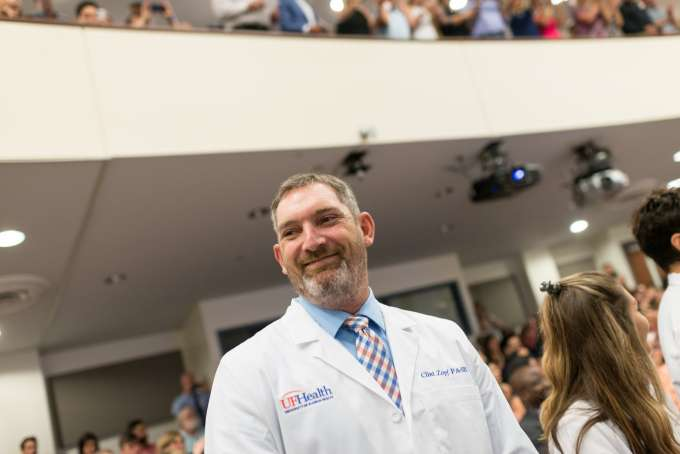 A student smiles while wearing his new white coat.