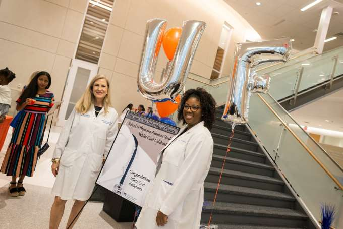 A student and faculty member pose with balloons that spell out U-F.