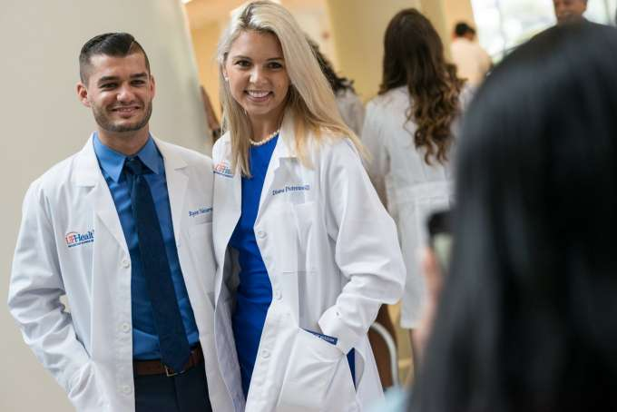Two students pose for a photo while wearing their new white coats.