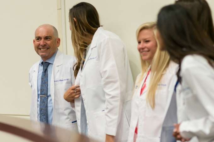 A group of four students converse while wearing their new white coats.