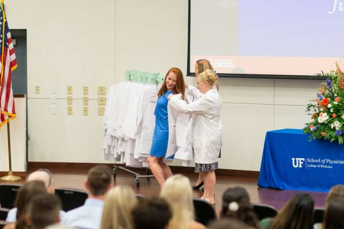 A faculty member helps a student put on her new white coat.