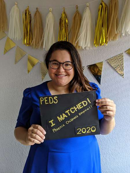 Agatha Matsos Formoso holds a sign announcing where she matched for residency training.