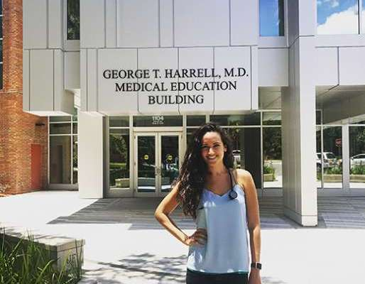 Christine Lalime stands in front of the Harrell Medical Education Building