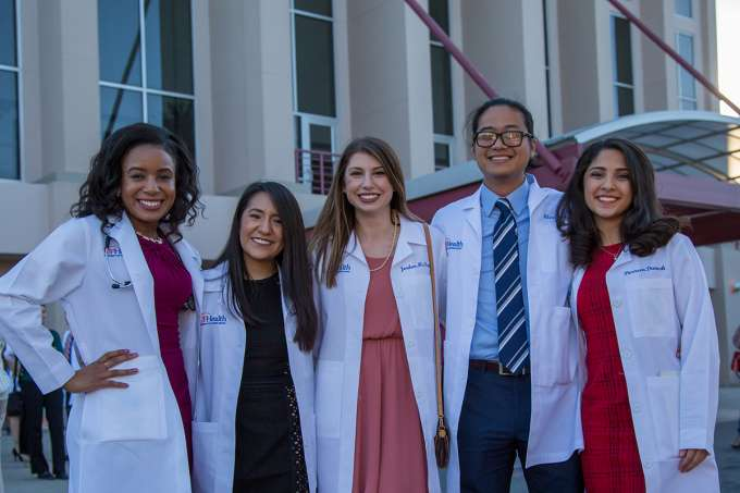 Five students pose for a photo while wearing their U-F Health white coats