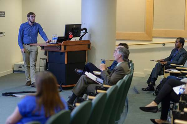 A student presents his research to an audience in a lecture hall
