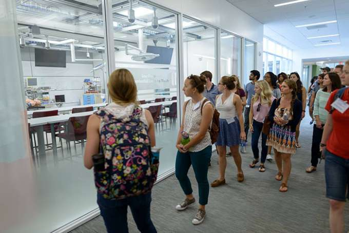 A group of students peeks into a room in the Harrell Building during a tour