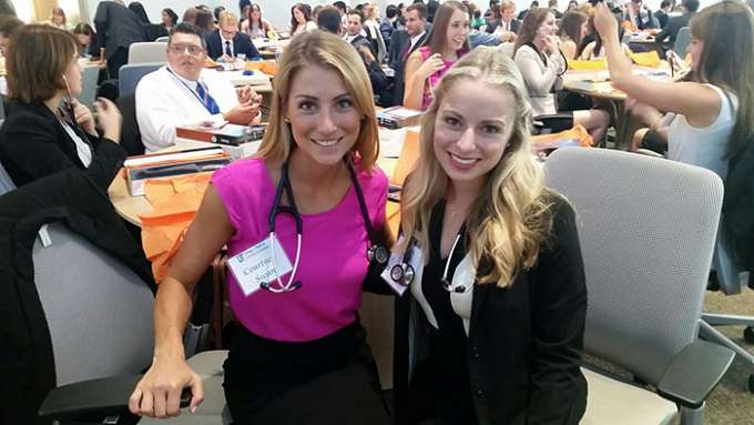 Two students pose with stethoscopes around their neck