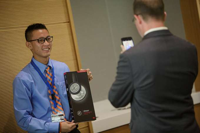 A man takes a photo of a student holding his stethoscope box.