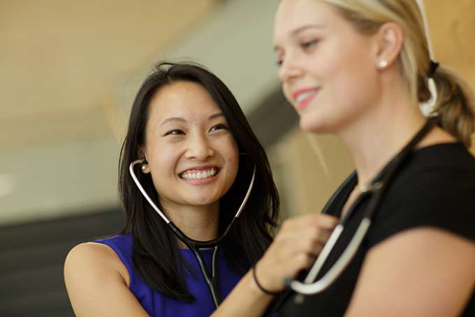 A student tries out her new stethoscope on a classmate.