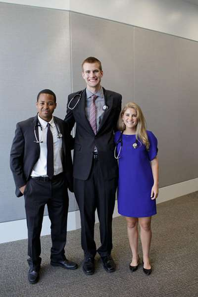 Three students in business attire pose for a photo with their new stethoscopes draped around their necks.