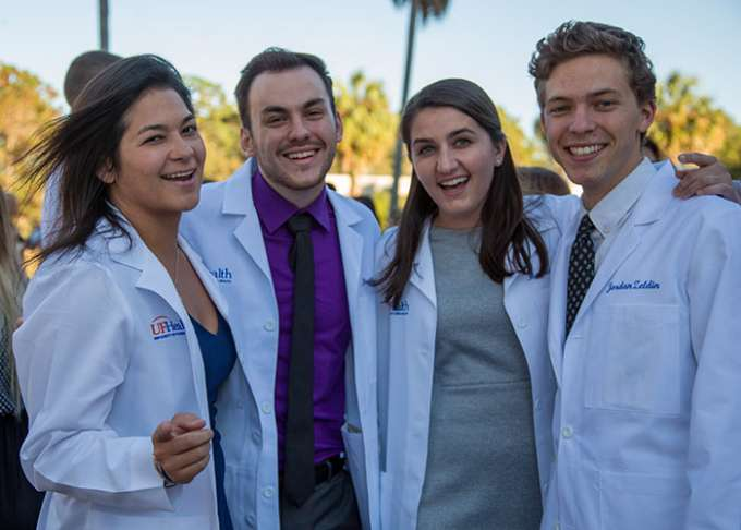 Four students pose for a photo outdoors while wearing their new white coats.