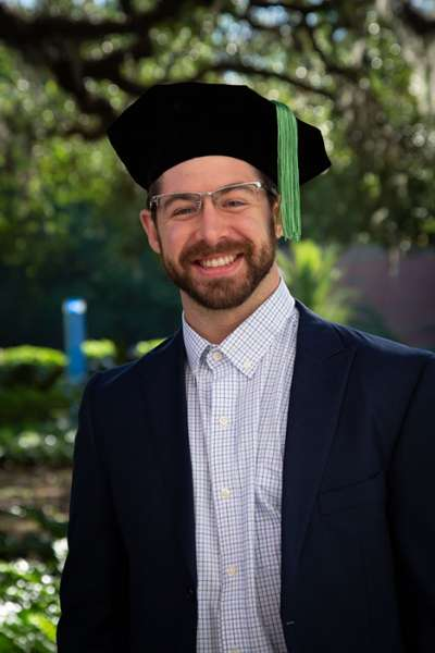 A graduate smiles outdoors while wearing a graduation cap