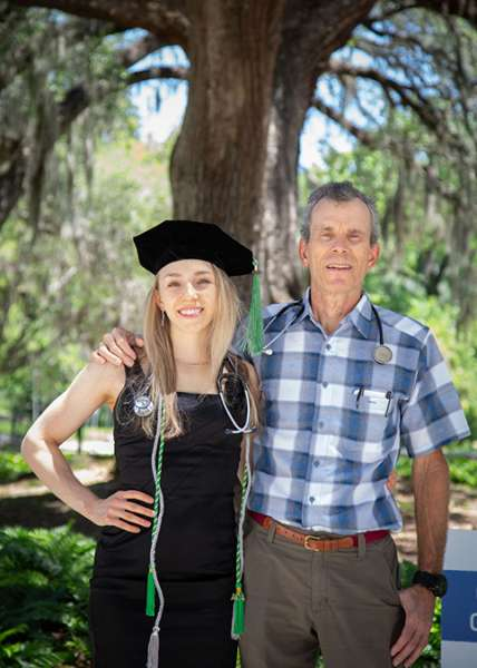 A graduate poses for a photo outside with her father.
