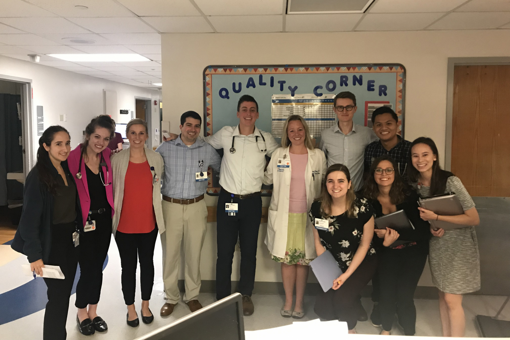 Ashleigh Wright, M.D. '07, center, in white coat, poses for a photo with third- and fourth-year medical students and residents during fall 2019.