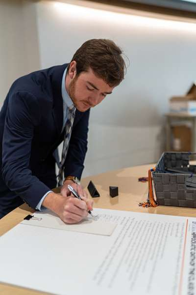 A graduate signs his name to the Hippocratic Oath