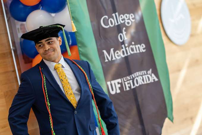 A graduate smiles while wearing a graduation cap and honors cords