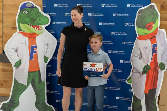 A graduate poses for a photo with her son against a U-F College of Medicine backdrop, along with cardboard cutouts of U-F mascots Albert and Alberta wearing white coats.