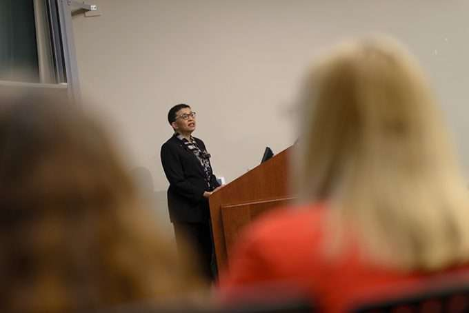 A woman stands at the front of a lecture hall to deliver a presentation.