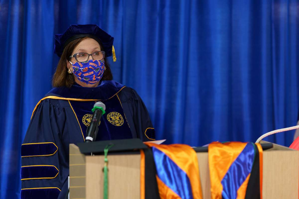 Nina Multak delivers her comencement speech at a podium while wearing commencement regalia and a blue U-F face mask.