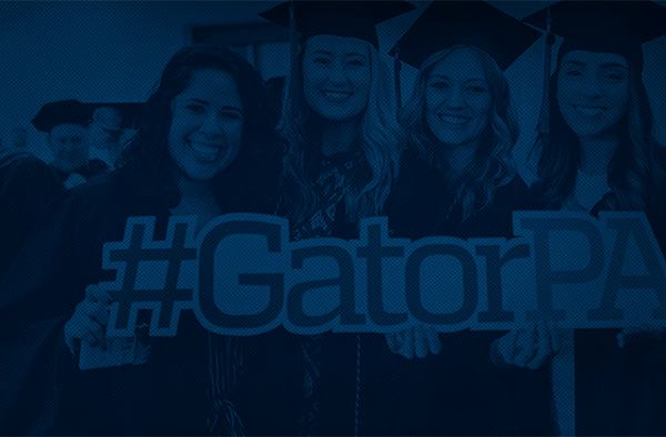 """Photo of four women in graduation caps and gowns holding a """"Gator P-A"""" sign"""