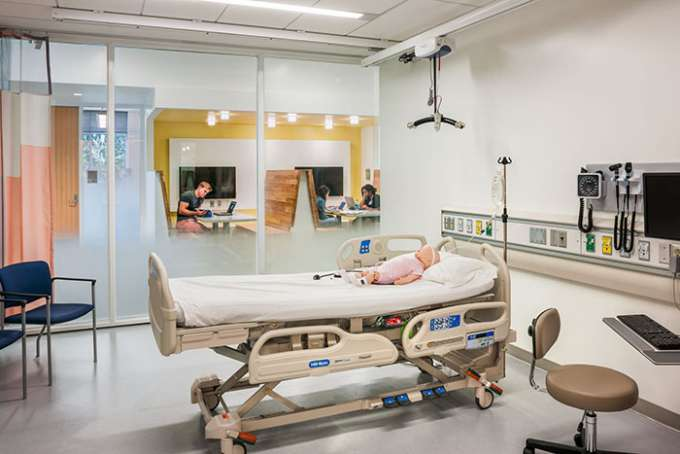 A mock hospital room with an infant human patient simulator on the patient bed.
