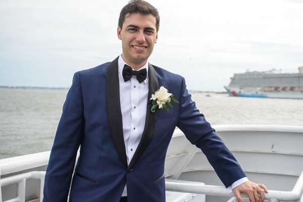 Theodore Drashansky wears a tuxedo while posing for a photo on a ship.