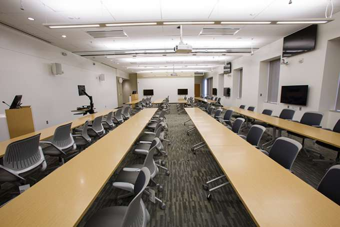 An empty classroom featuring three rows of rectangular tables and chairs.