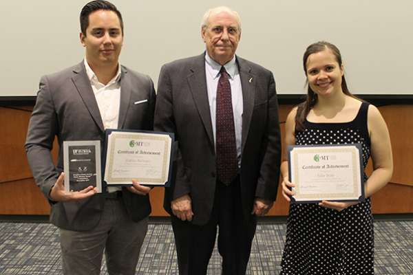 Two students pose with a faculty member while holding awards.