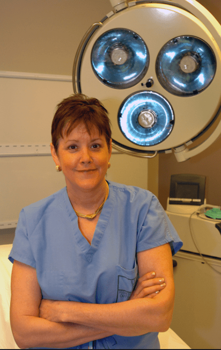 Suzanne Klimberg crosses her arms while wearing blue scrubs in an operating room.